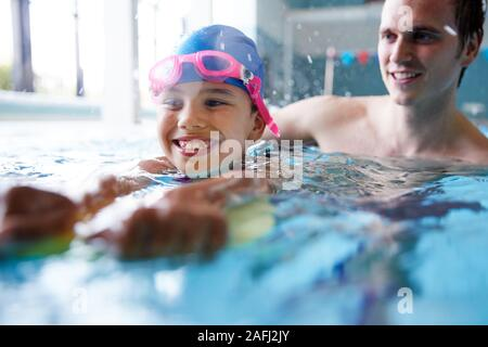 Male Swimming Coach Giving Girl Holding Float One To One Lesson In Pool