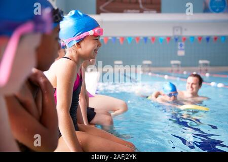 Male Coach In Water Giving Group Of Children Swimming Lesson In Indoor Pool - Stock Photo