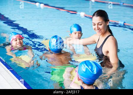 Female Coach In Water Giving Group Of Children Swimming Lesson In Indoor Pool