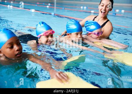 Female Coach In Water Giving Group Of Children Swimming Lesson In Indoor Pool - Stock Photo