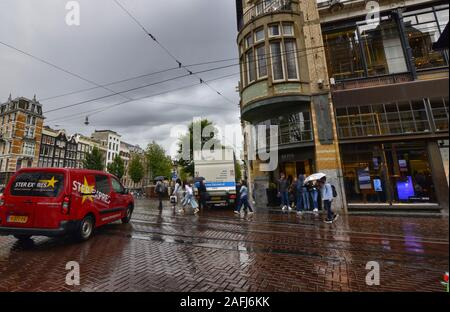 Amsterdam, Holland, August 2019. Rainy day in the old town. The silhouettes of people and things are reflected on the wet road. People cross the cross - Stock Photo
