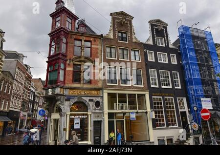Amsterdam, Holland, August 2019. Rainy day in the old town. Among the typical little houses, a corner with a red bay window attracts the untidy standi - Stock Photo