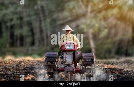 Woman farmer using the walking tractor to plow for rice plant in rainy at beautiful the sun setting over in the background, Rural Countryside of Thail - Stock Photo
