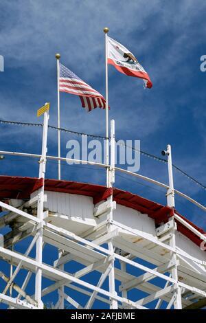 American and Californian flag on the Big Dipper wooden roller coaster at Santa Cruz Beach Boardwalk Amusement Park, Santa Cruz, California, USA - Stock Photo