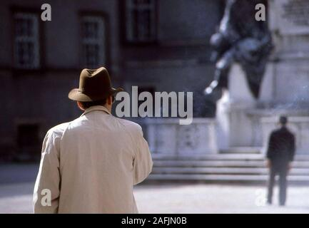 Smoking man with hat and coat in front of the Pferdebrunnen (Fountain) in Salzburg.