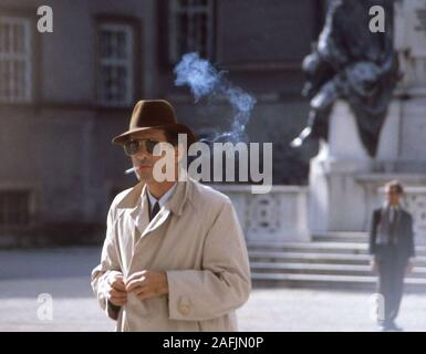 Smoking man with hat, sunglasses and coat in front of the Pferdebrunnen (Fountain) in Salzburg.