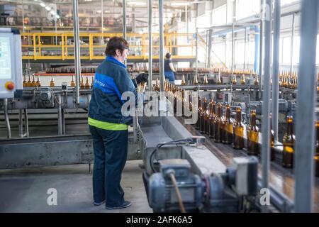 Operator monitors moving empty bottles on conveyor - Stock Photo