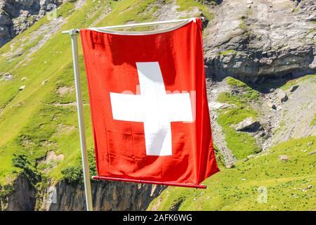 Waving National Flag Of Switzerland With Blurred Alpine Landscape