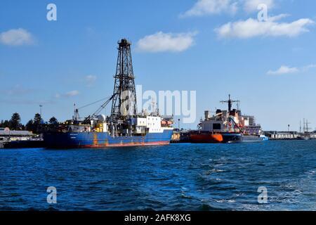 Perth, WA, Australia - November 27, 2017: Drill ship and freighter on pier at Fremantle harbor - Stock Photo