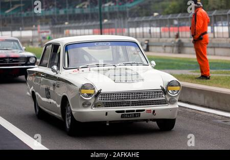 A 1965, White, Ford Lotus Cortina, exiting the pit lane during the Transatlantic Trophy for Pre '66 Touring Cars, at the 2019 Silverstone Classic - Stock Photo
