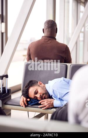 Businessman Sleeping On Seats In Airport Departure Lounge Because Of Delay - Stock Photo