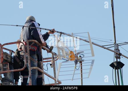 Worker on telescopic elevator repairing a antenna with blue sky on background. Communication maintenance - Stock Photo