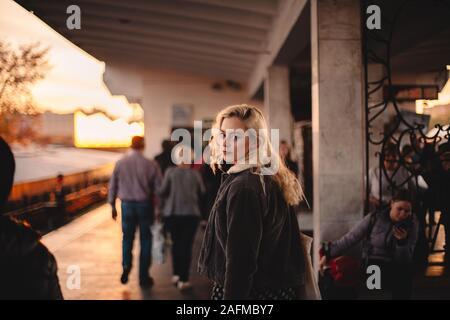 Young woman looking back at camera walking on subway station - Stock Photo