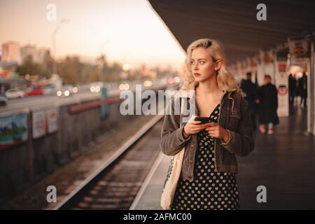 Young thoughtful woman using smart phone while waiting for train - Stock Photo