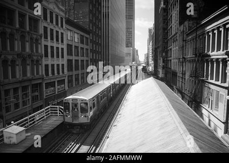 Chicago, Illinois, USA - 1996:  Archival black and white view of downtown architecture and commuter train and elevated tracks along Wabash Ave. - Stock Photo