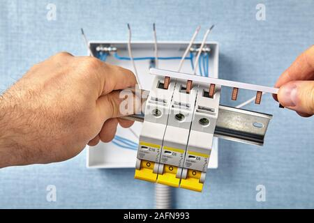 A technician mounts an electrical cabinet or switchboard in a residential area. A repairman connects circuit breakers, also called fuses, using a busb - Stock Photo