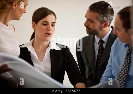 Small group of business people in a meeting looking at building plans. - Stock Photo
