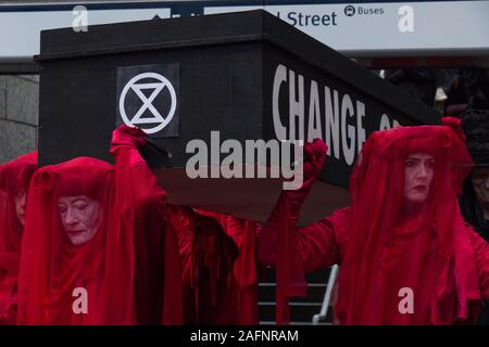 Vancouver, Canada - Nov 29, 2019: A group Extinction Rebellion is hosting a Funeral for Extinction wearing red dresses near Burrard Sky Train Station - Stock Photo