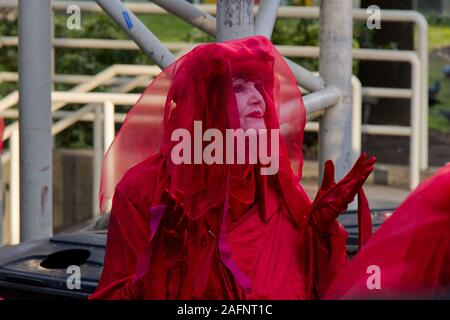 Vancouver, Canada - November 29,2019:A member of extinction rebellion dressed in red robe walks with palms held up near Burrard Station - Stock Photo