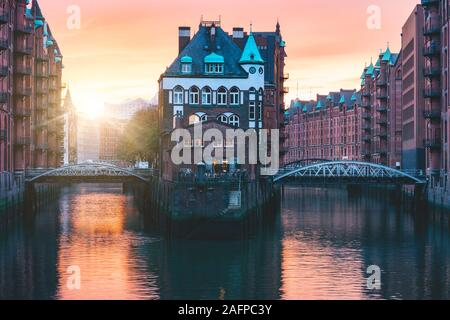 Hamburg city old port, Germany, Europe. Historical famous warehouse district with water castle palace at sunset golden light