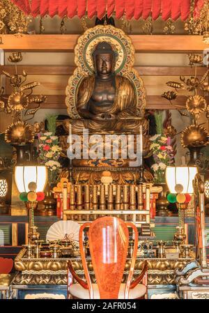 Golden statue depicting the buddha Shaka Nyorai behind the fusuma paper panel of the Tendai Buddhism Tennoji temple in the Yanaka cemetery of Tokyo. - Stock Photo