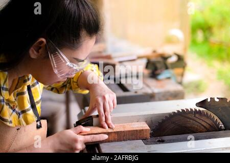 Women standing is craft working cut wood at a work bench with circular saws power tools at carpenter machine in the workshop - Stock Photo