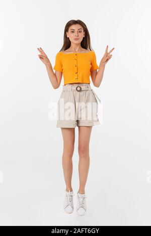 Portrait of a joyful woman jumping in the studio with happy feeling, isolated on white background, 20-28 year old - Stock Photo