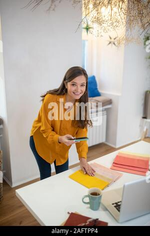 Positive cheerful woman taking photos of samples - Stock Photo