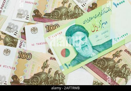 A macro image of a green ten thousand rial bank note from Iran on a bed of Russian one hundred ruble bank notes close up - Stock Photo