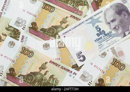 A close up image of a purple five Turkish lira bank note on a background of Russian one hundred ruble bank notes in macro - Stock Photo