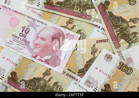 A close up image of a red ten Turkish lira bank note on a background of Russian one hundred ruble bank notes in macro - Stock Photo