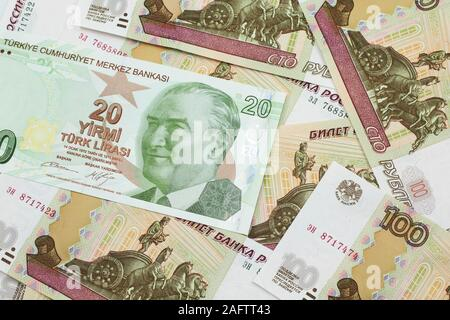 A close up image of a green twenty Turkish lira bank note on a background of Russian one hundred ruble bank notes in macro - Stock Photo