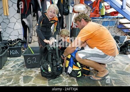 Children discover scuba diving, scuba instructor helps children to prepare diving equipment, Zakynthos island, Greece - Stock Photo