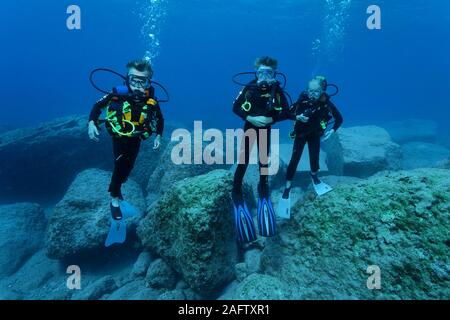 Children discover scuba diving at a rocky reef, Zakynthos island, Greece - Stock Photo