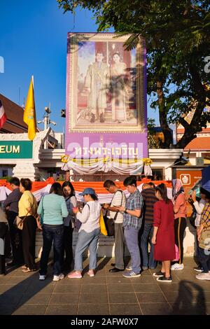 Visitors in front of the National Museum in Bangkok, Thailand, and under a portrait of the royal Thai couple, awaiting the museum's morning opening - Stock Photo