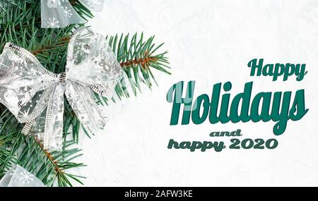 Flat lay composition with the lettering, happy holidays and happy 2020. Frame with christmas tree branches, christmas decorations, balls, hearts - Stock Photo