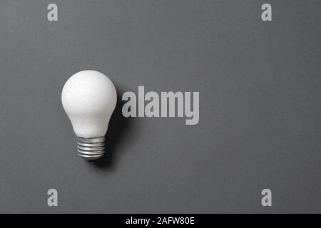 Creativity inspiration, great business idea concept with white light bulb on black background. Flat lay, top view, copy space - Stock Photo