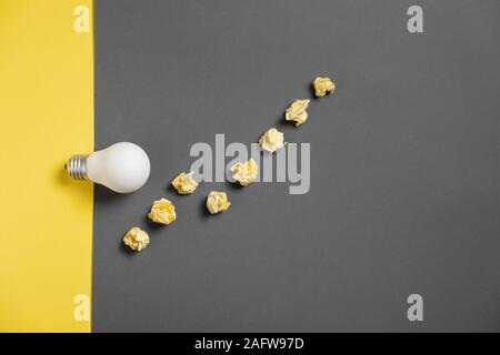 New idea concept with crumpled office paper and white light bulb on black and yellow background. creative solution during brainstorming session. Flat - Stock Photo