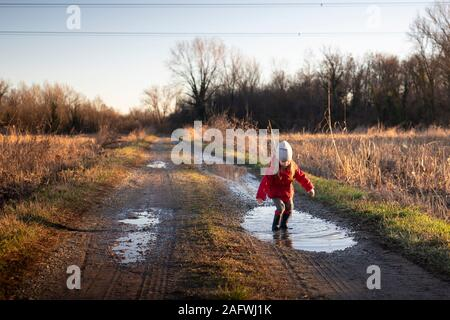 3 years old child jumping in a puddle with red jacket and wellies on a sunny winter day. Golden hour light. - Stock Photo