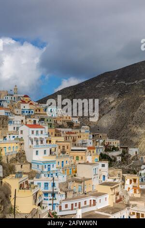 A vertical picture of colorful houses in Karpathos surrounded by mountains under a cloudy sky - Stock Photo