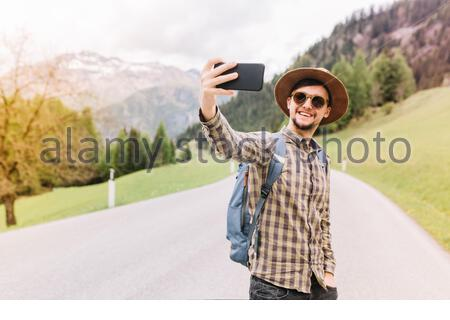 Young man wearing hat and trendy sunglasses making selfie during his travel with amazing mountain landscape on background. Self-portrait of smiling guy in checkered shirt with backpack on the highway. - Stock Photo