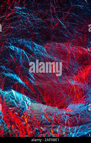 Crumpled red-blue foil paper with textured surface.Texture or background