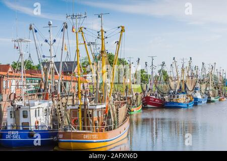 Trawlers in the historic fishing harbor of Greetsiel in Eastern Frisia, Germany - Stock Photo
