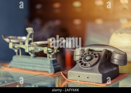 The old black telephone with rotary dial with dust and scratches placed on a clear glass cabinet in an ancient pharmacy. - Stock Photo