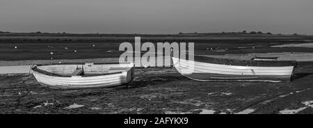 Mono chrome of rowing boats stranded on the mud at low tide, seen at Brancaster Staith, Norfolk, UK. Taken 3rd DEc 2019. - Stock Photo
