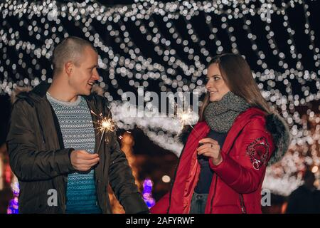Young happy couple  holding hands having fun with  sparklers in winter city night. - Stock Photo