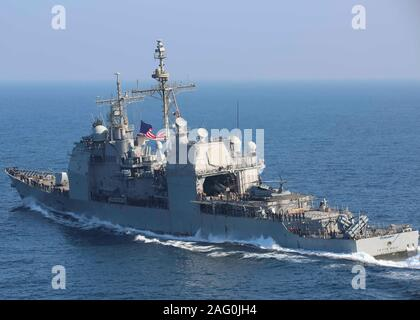 A U.S. Navy Ticonderoga-class guided-missile cruiser USS Leyte Gulf sails in formation alongside the aircraft carrier USS Abraham Lincoln December 10, 2019 in the Arabian Sea. - Stock Photo