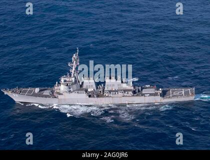 A U.S. Navy Arleigh Burke-class guided-missile destroyer USS Barry sails in formation during a maneuvering exercise November 29, 2019 in the East China Sea. - Stock Photo