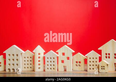 Miniature wooden houses on a red background. Real estate concept. City. Agglomeration and urbanization. Market Analytics. Demand for housing. Rising a - Stock Photo