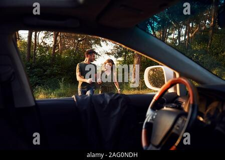 View from the car's interior. Steering wheel, side mirror. Beautiful young couple have a good time in the forest at daytime